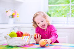 Little girl eating apples Royalty Free Stock Image