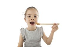 Little girl eating Asian cookies. Portrait of young girl who is eating Asian cookies with a chopsticks, isolated on white Royalty Free Stock Photo