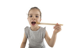 Little girl eating Asian cookies. Portrait of young girl who is eating Asian cookies with a chopsticks, isolated on white Royalty Free Stock Photography
