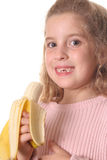 Little girl eating a banana. Shot of a little girl eating a banana Stock Photo