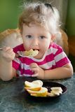 Little  girl eating banana and apple Royalty Free Stock Photos
