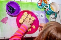 Little girl eating banana bread for breakfast stock images