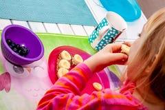 Little girl eating banana bread for breakfast royalty free stock photos