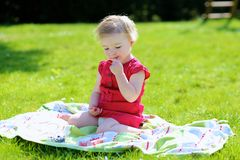 Little girl eating berries in the garden Stock Photos