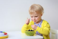Little girl eating berries Stock Image
