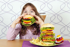 Little girl eating a big hamburger Royalty Free Stock Photo