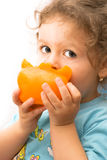 Little girl eating a big pepper Stock Photos