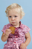 Little girl eating a biscuit. Royalty Free Stock Images