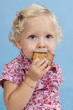 Little girl eating a biscuit. Royalty Free Stock Image