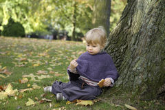 Little girl eating a biscuit , outdoors in the park Stock Photos
