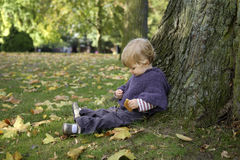 Little girl eating a biscuit , outdoors in the park Stock Image