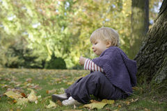 Little girl eating a biscuit , outdoors in the park Royalty Free Stock Photography