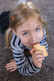 Little girl eating biscuits on the carpet. Repaired girls. Stock Photo