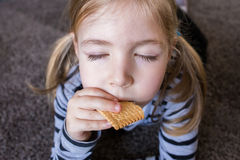 Little girl eating biscuits on the carpet. Repaired girls. Stock Photography