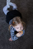 Little girl eating biscuits on the carpet. Repaired girls. Royalty Free Stock Image