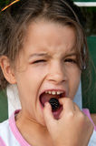 Little girl eating a blackberry Royalty Free Stock Images