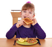 Little girl eating bread Stock Photos