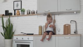 Little girl eating bread in the kitchen stock video