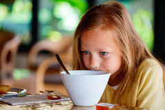 Little girl eating breakfast Royalty Free Stock Photos