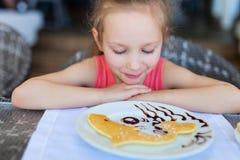 Little girl eating breakfast Stock Images