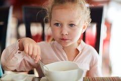 Little girl eating breakfast Stock Photos