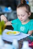 Little girl eating breakfast Royalty Free Stock Photos
