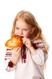 Little girl eating bun with big appetite. Royalty Free Stock Photo