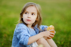 Little girl eating a bun outdoors Royalty Free Stock Images