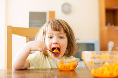 Little girl eating carrot salad Royalty Free Stock Photography