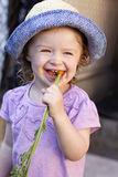 Little girl eating carrot Stock Image