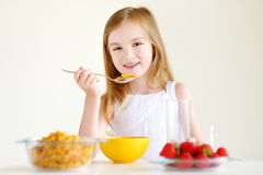 Little girl eating cereal with milk Stock Photography