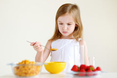 Little girl eating cereal with milk Royalty Free Stock Photo