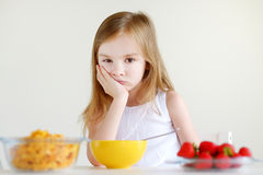 Little girl eating cereal with milk Royalty Free Stock Photos