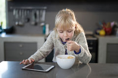 Little girl eating cereals rings with spoon from a bowl Royalty Free Stock Photo