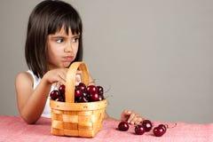 Little girl eating cherries Stock Photo