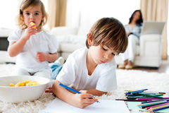Little girl eating chips and her brother drawing Royalty Free Stock Photos