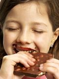 Little girl eating chocolate. Stock Images