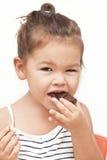 Little girl eating chocolate. Asian little girl eating chocolate Stock Image