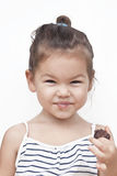 Little girl eating chocolate. Asian little girl eating chocolate Royalty Free Stock Photography