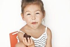 Little girl eating chocolate. Asian little girl eating chocolate Stock Photos