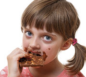Little girl eating chocolate Stock Images