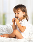 Little girl eating chocolate candy in bed. Little cute girl eating chocolate candy in bed Stock Photo