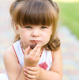 Little girl is eating chocolate candy. Outdoor shoot Royalty Free Stock Images