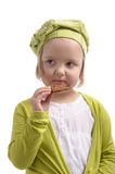 Little girl eating a chocolate cookie. Isolated on white Stock Image