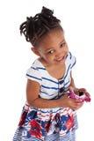 Little girl eating chocolate easter egg. Little african american girl eating chocolate easter egg, isolated on white background Stock Photo