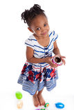 Little girl eating chocolate easter egg. Little african american girl eating chocolate easter egg, isolated on white background Royalty Free Stock Image