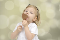 Little girl eating a chocolate lollypop Royalty Free Stock Photos