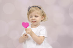 Little girl eating a chocolate lollypop Stock Images