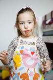 Little girl eating chocolate off the mixer beater Royalty Free Stock Images