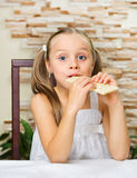 Little girl eating an chocolate. At the table Royalty Free Stock Photo
